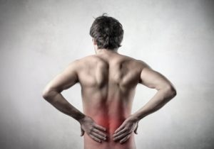 13655194 - rear view of a bare-chested man suffering from backache