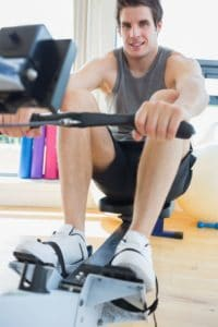 15591175 - man working out on row machine in fitness studio