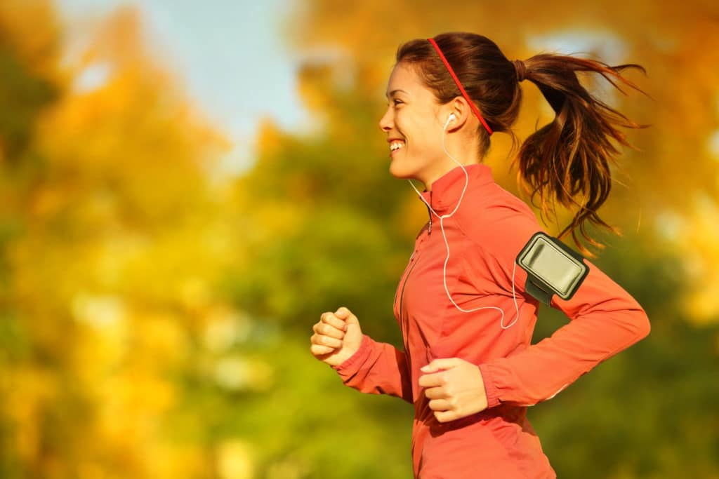 32442088 - woman runner running in fall autumn forest listening to music on smartphone using earphones. female fitness girl jogging on path in amazing fall foliage landscape nature outside.