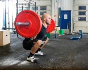 33583305 - male athlete lifting barbell at gym