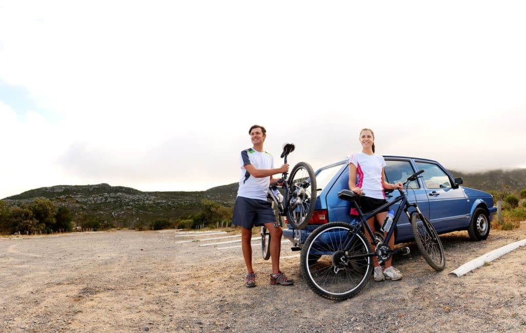 12347330 - panorama of a couple who have finished mountain biking outdoors and are loading the bicycles onto the car bike rack. large image, lots of copyspace, healthy lifestyle scene.